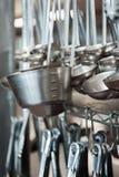 Строки серебряных ковшей вися в кухне стоковая фотография rf