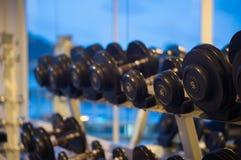 Строки черных гантелей в спортзале на вечере Стоковое Изображение
