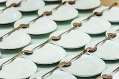 Строки чистых белых блюда и ложки в столовой или ресторане готовых для служения Стоковая Фотография