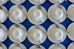 Строки чистых белых вверх ногами чашек, блюда и ложки в столовой или ресторане готовых для служения горячего напитка, полного bac Стоковая Фотография