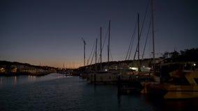 Строки шлюпок на пристани в вечере против небес захода солнца видеоматериал