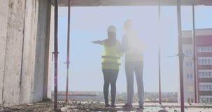 Строя работники работая на строительной площадке, построители смотря в светокопии, заднем взгляде, космосе экземпляра E видеоматериал