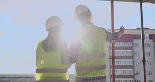Строя работники работая на строительной площадке, построители смотря в светокопии, заднем взгляде, космосе экземпляра E акции видеоматериалы