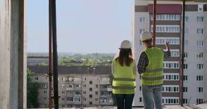 Строя работники работая на строительной площадке, построители смотря в светокопии, заднем взгляде, космосе экземпляра E сток-видео