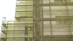 Строя реновация фасада, старая реконструкция дома, ремонт Ремонтина перед строя фасадом покрытым с желтое прозрачным сток-видео
