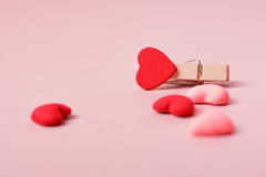Струбцина и малые сердца на свете - розовой предпосылке Стоковая Фотография
