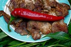 Стручок красного перца на зажаренном мясе на плите Стоковые Изображения