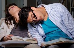2 студента изучая поздно подготавливать для экзаменов стоковая фотография
