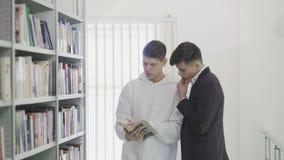 2 студента ищут книга на книжных полках на библиотеке на коллеже сток-видео