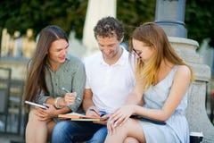 3 студента подготавливают для экзаменов Стоковое Фото
