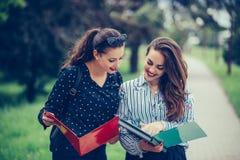 2 студента уча читающ тетрадь и комментирующ в улице стоковое изображение