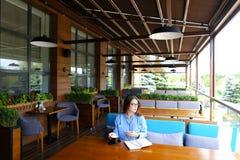 Студентка в стеклах выпивая кофе на кафе и сидя с smartphone и тетрадью Стоковое Изображение RF