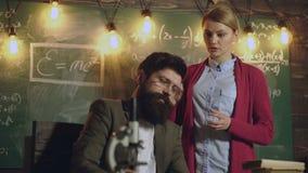 Студентка обсуждает с бородатым учителем в стеклах стоя около зеленого школьного правления на котором различный видеоматериал