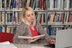 Студентка печатая на компьтер-книжке в университетской библиотеке Стоковое фото RF