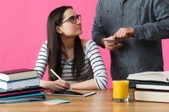 Студентка работая одно к одно с гувернером Студент порции гувернера, который нужно подготовить для экзаменов Стоковая Фотография