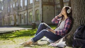 Студентка сидя на траве, полагающся против дерева, слушая к музыке, ослабляет Стоковое Изображение RF