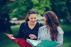 2 студентки уча читающ тетрадь и комментирующ в улице стоковые фото