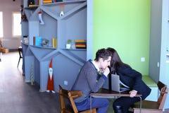 Студенты Гая и девушки ослабляют в библиотеке после школы и сидят на t Стоковые Фотографии RF