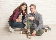 Студенты Гая и девушки сидят на поле стоковые фото