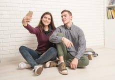 Студенты Гая и девушки сидят на поле стоковая фотография rf