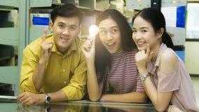 Студенты группы людей держат электрическую лампочку с светлым insi Стоковая Фотография RF