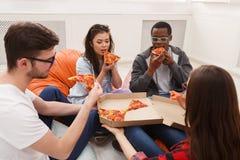 Студенты деля партию пиццы дома Стоковые Фото