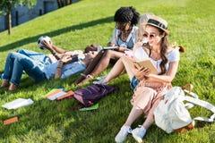 Студенты изучая и отдыхая на зеленой траве в парке Стоковые Фотографии RF