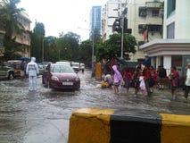 Студенты имеют потеху на день дождя на затопленной дороге Мумбая стоковые фото