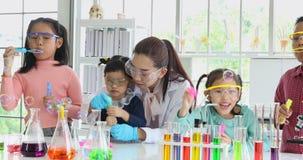 Студенты и пузыри учителя дуя в лаборатории сток-видео