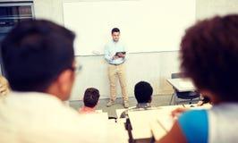 Студенты и учитель с ПК планшета на лекции стоковые фото
