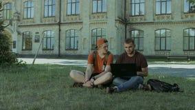 Студенты колледжа работая на компьтер-книжке на лужайке кампуса акции видеоматериалы