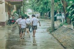 Студенты мальчика выходят класс для того чтобы идти на улицу после проливного дождя стоковая фотография