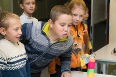 Студенты начальной школы дуют на домодельном вентиляторе стоковые изображения