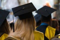 Студенты нося мантии и шляпы сидя внутри помещения, ждущ к rece стоковые изображения