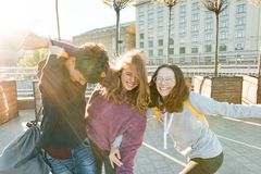 Студенты подростков друзей с сумками школы, имеющ потеху на пути от школы Предпосылка города, золотой час стоковые фотографии rf