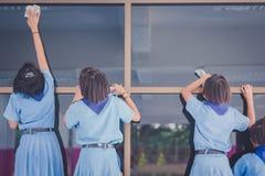Студенты помогают обтереть стекло стоковое фото