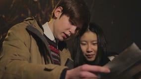 Студенты потеряли в чужом городе, смотрящ карту, проверяя правильное направление, туризм видеоматериал