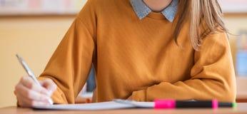 Студенты принимая экзамен в классе Испытание образования, концепция экзаменов Знамя сети стоковые фото