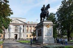Студенты проверяют и сфотографировали против фона памятника к Питеру i около замка Mikhailovsky Стоковые Фото