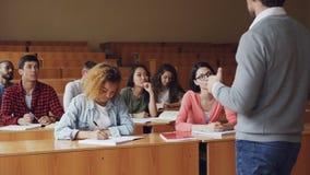 Студенты средней школы имеют урок с мужским учителем, молодые люди пишущ и говорящ обучать сидеть на видеоматериал