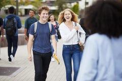 Студенты средней школы общаясь внешние здания коллежа стоковое изображение rf