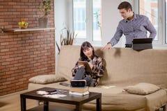 Студенты уча для рассмотрений вместе с eBook в домашнем интерьере Стоковая Фотография