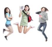 студенты excited группы девушки скача стоковые изображения