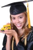 Студент-выпускник с моделью школьного автобуса Стоковая Фотография