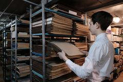 Студент в библиотеке или в комнате архива ищет информация Школьник в белой рубашке вытягивает вне старую книгу стоковая фотография