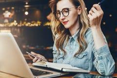 Студент в ультрамодных стеклах сидит в кафе перед компьтер-книжкой, наблюдает воспитательное webinar Коммерсантка работая удаленн стоковое фото