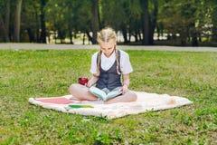 Студент в форме есть красное яблоко на обед школьница сидя на одеяле в парке с книгами стоковые фотографии rf