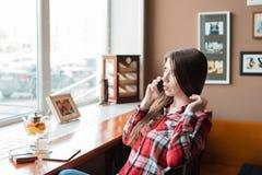 Студент девушки в рубашке шотландки, в после полудня на кафе окном, говоря на телефоне, чайник с кружкой  Стоковые Изображения RF