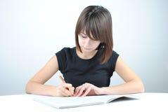 студент девушки пишет Стоковые Фотографии RF