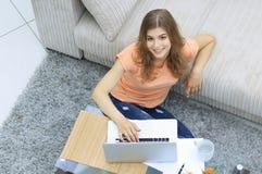 Студент девушки работая на компьтер-книжке сидя на ковре около софы Стоковая Фотография